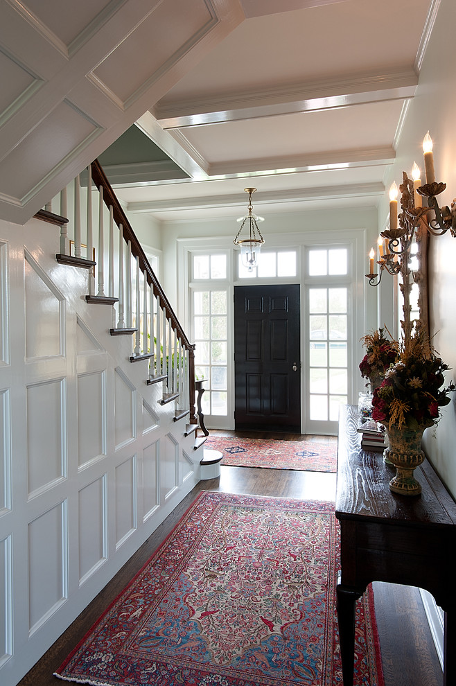 Example of a mid-sized classic dark wood floor entryway design in Dallas with a black front door and white walls