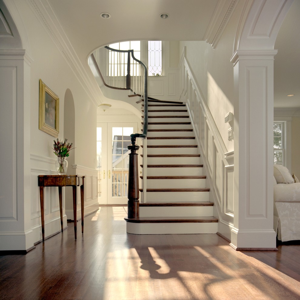 Huge elegant medium tone wood floor entryway photo in DC Metro with white walls and a glass front door