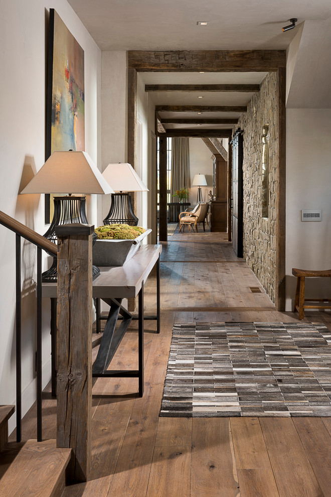 Inspiration for a rustic medium tone wood floor foyer remodel in Other with white walls