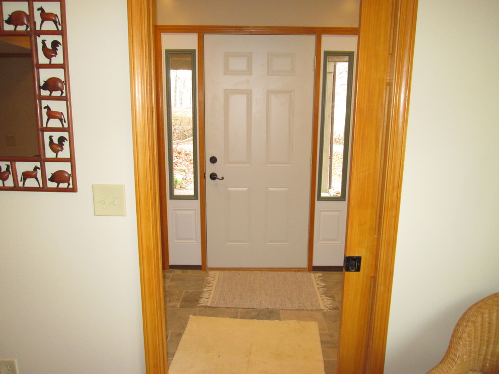 Mid-sized farmhouse ceramic tile entryway photo in Indianapolis with beige walls and a white front door