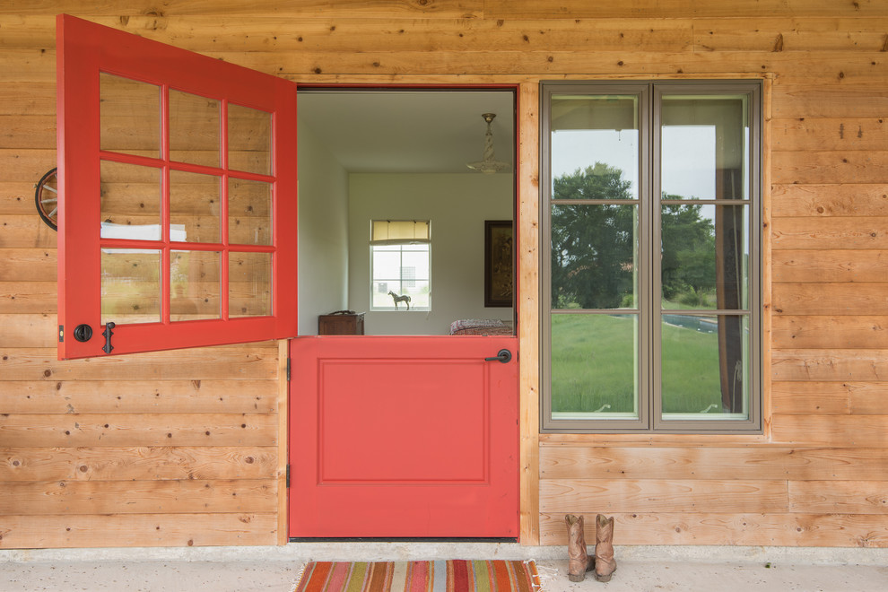 Country entryway photo in Austin with a red front door