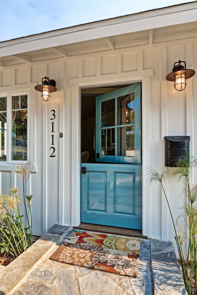 Mid-sized coastal limestone floor entryway photo in Los Angeles with a blue front door and white walls