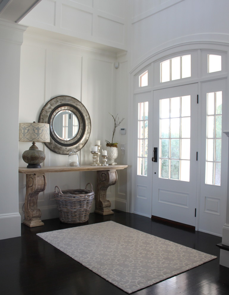 This is an example of a nautical entrance in Boston with dark hardwood flooring, a single front door and a white front door.