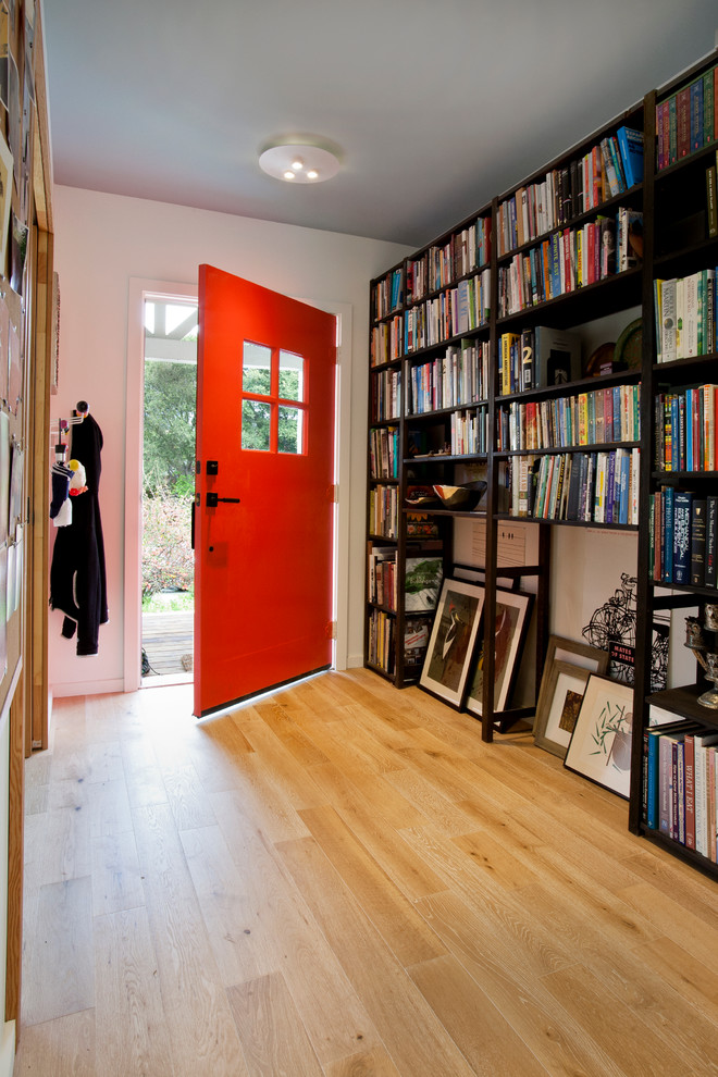 Example of a small trendy light wood floor entryway design in San Francisco with white walls and a red front door