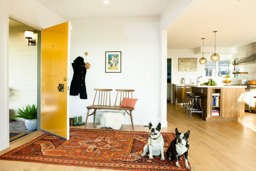 Example of a mid-sized mid-century modern light wood floor entryway design in San Francisco with white walls and a yellow front door