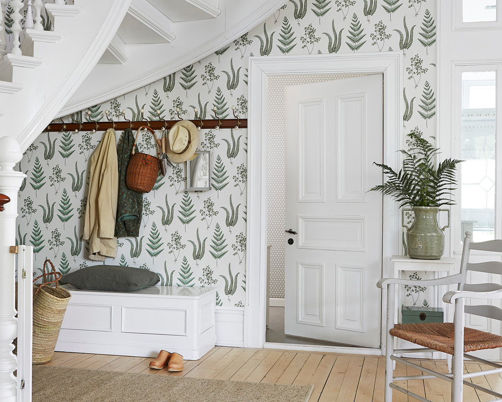 Inspiration for a mid-sized cottage light wood floor entryway remodel in Boston with green walls and a white front door