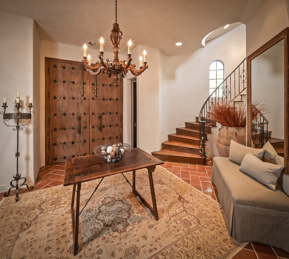 Example of a tuscan terra-cotta tile entryway design in Houston