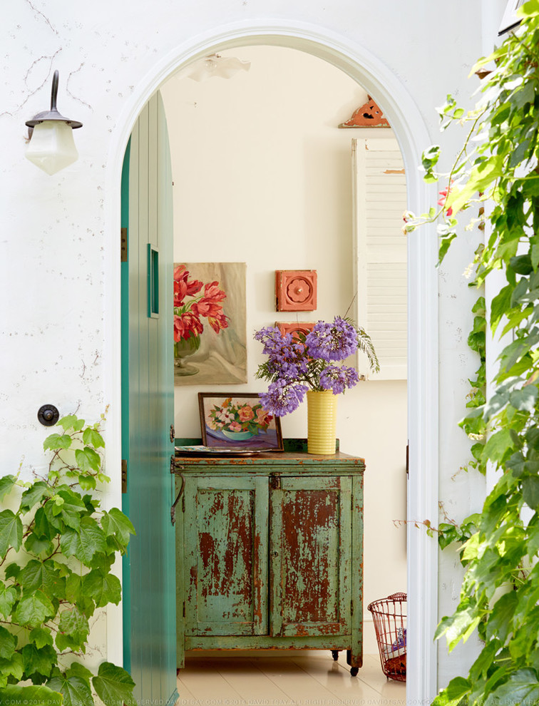 Example of a small cottage chic entryway design in Los Angeles with white walls and a green front door