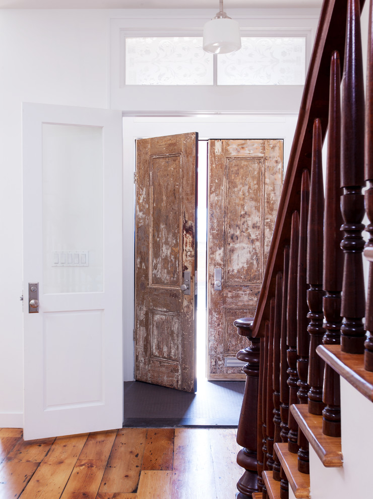 Mid-sized trendy medium tone wood floor entryway photo in New York with white walls and a medium wood front door
