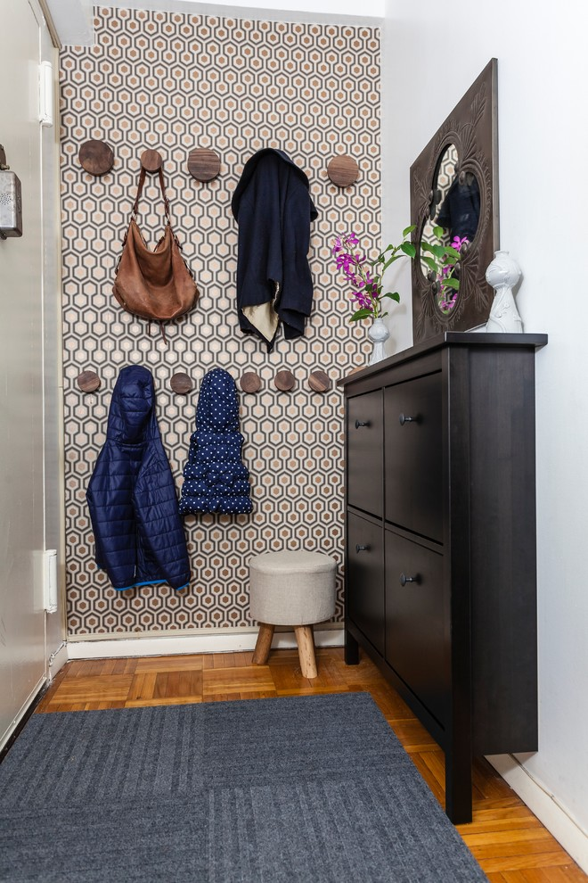 Inspiration for a small transitional medium tone wood floor entryway remodel in New York with a white front door and metallic walls