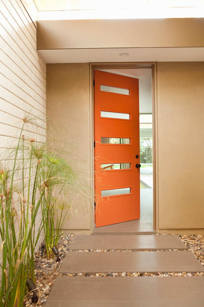 Inspiration for a retro entrance in Los Angeles with an orange front door.