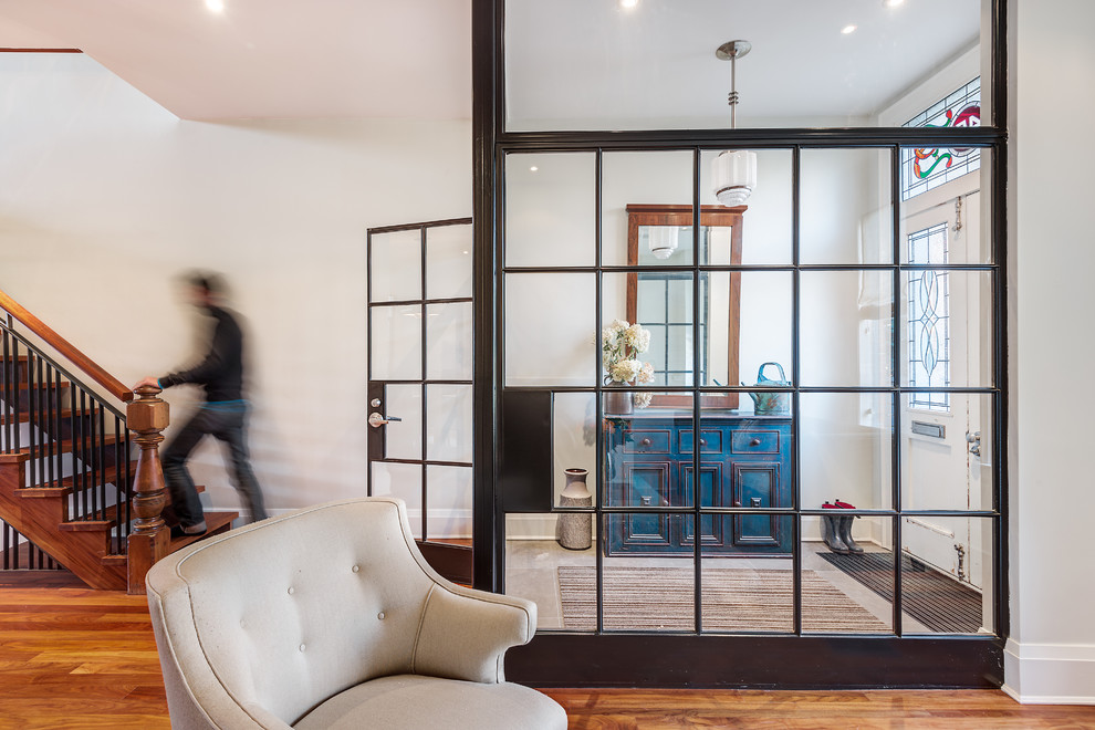 Entryway - mid-sized industrial light wood floor entryway idea in Toronto with white walls and a white front door