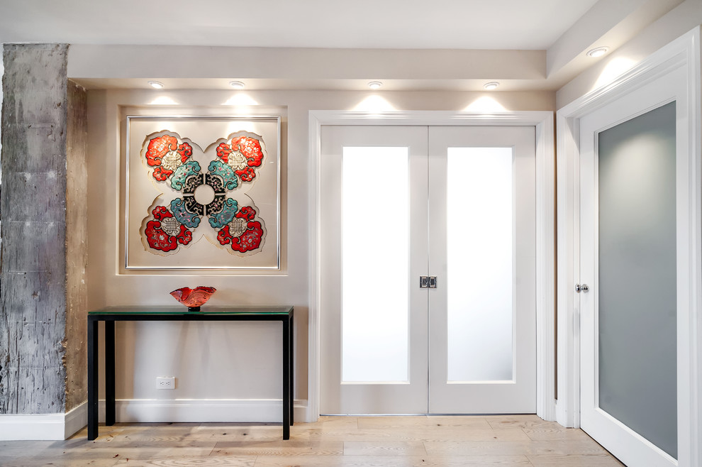 Mid-sized transitional light wood floor entryway photo in New York with gray walls and a glass front door