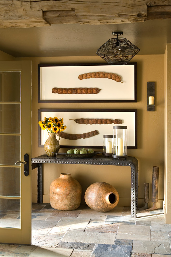 Entryway - small rustic ceramic tile entryway idea in Other with brown walls