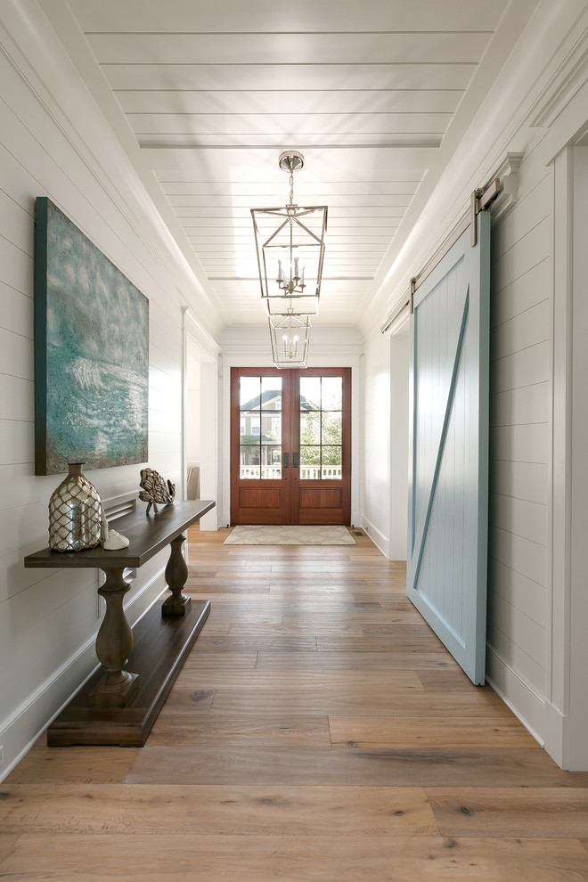 Example of a beach style beige floor entry hall design in Charleston