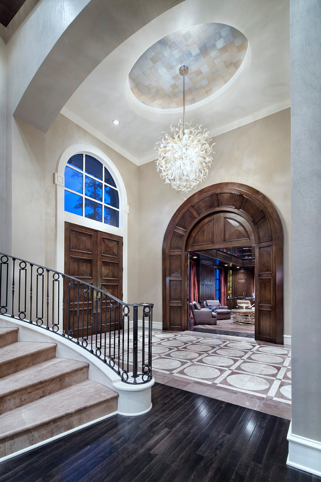 Example of a classic entryway design in Houston with beige walls and a dark wood front door