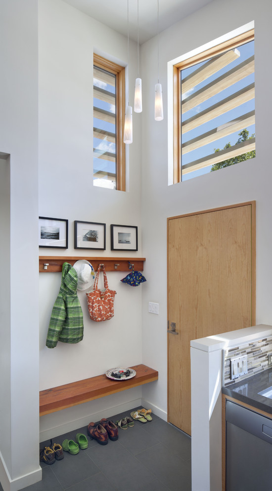 Entryway - contemporary porcelain tile entryway idea in San Francisco with white walls and a light wood front door