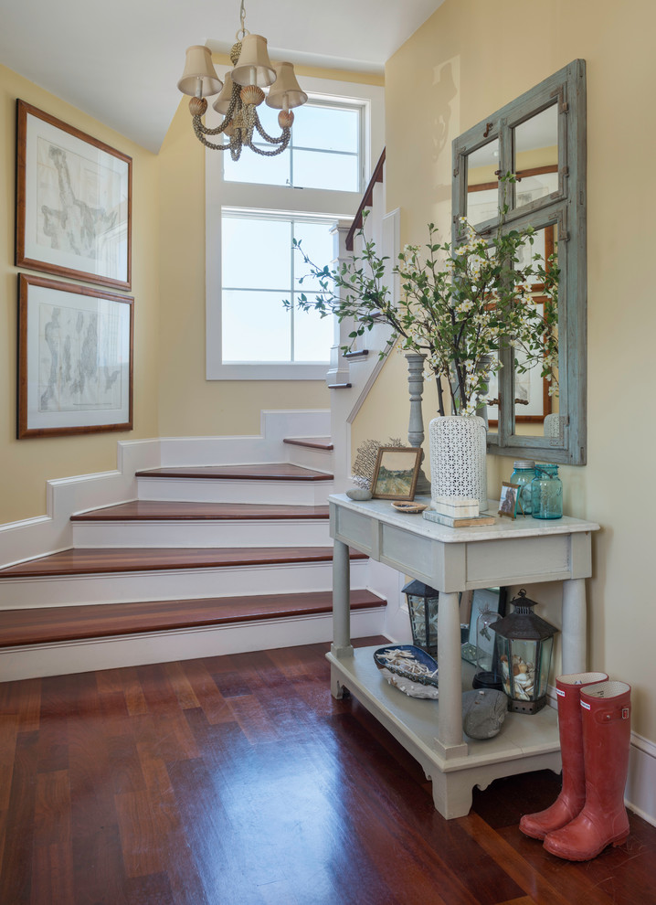 Inspiration for a mid-sized coastal medium tone wood floor foyer remodel in Providence with yellow walls