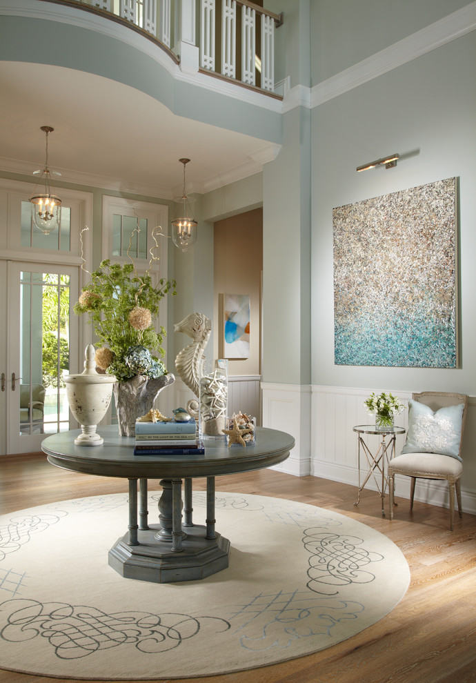 Example of an island style foyer design in Tampa with blue walls and a glass front door