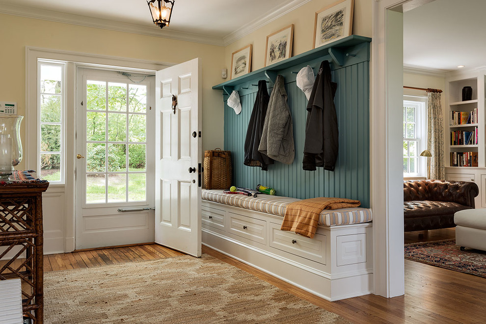 Elegant medium tone wood floor entryway photo in New York with a white front door and yellow walls