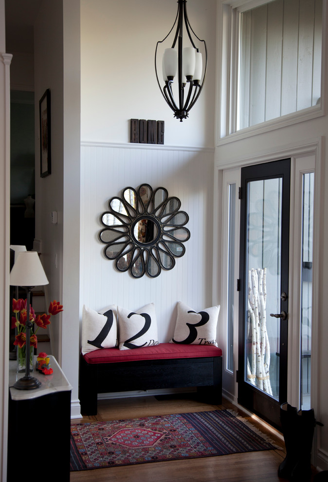 Inspiration for a small timeless medium tone wood floor entryway remodel in Vancouver with white walls and a black front door