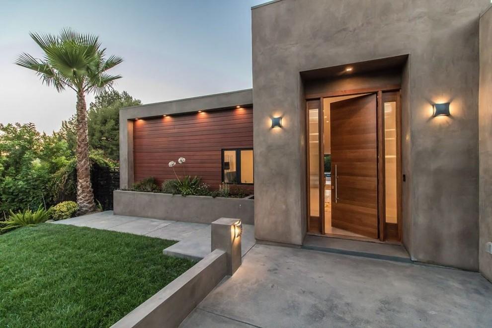 Trendy concrete floor and gray floor entryway photo in Los Angeles with gray walls and a medium wood front door