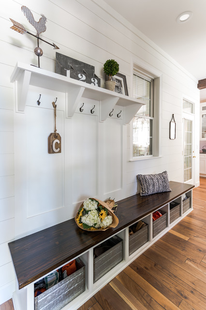 Farmhouse medium tone wood floor and brown floor mudroom photo in Raleigh with white walls