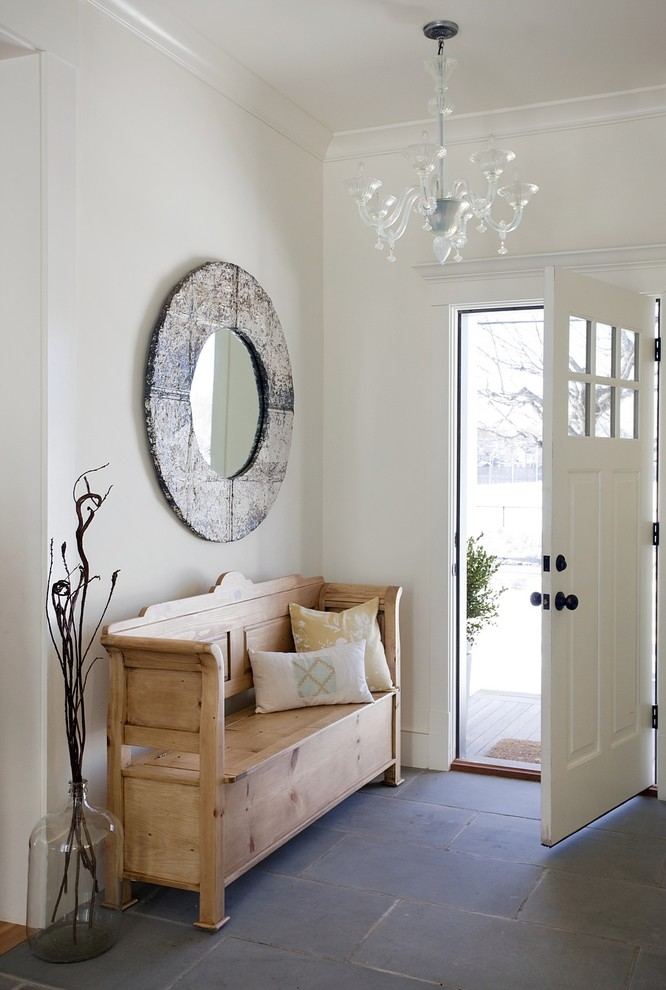 Example of a beach style gray floor single front door design in Boston with white walls and a white front door