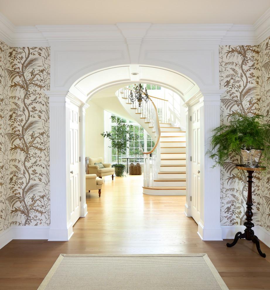 Imagen de entrada tradicional con paredes blancas, suelo de madera en tonos medios y suelo marrón