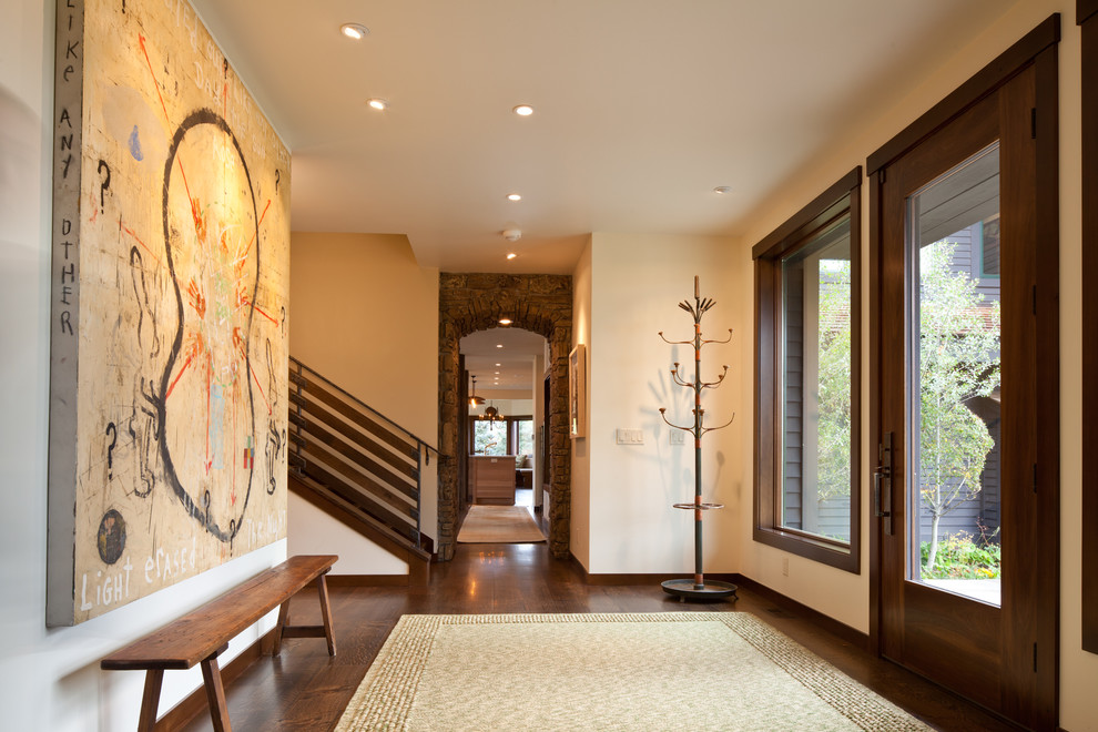 Inspiration for a contemporary dark wood floor entryway remodel in Denver with beige walls
