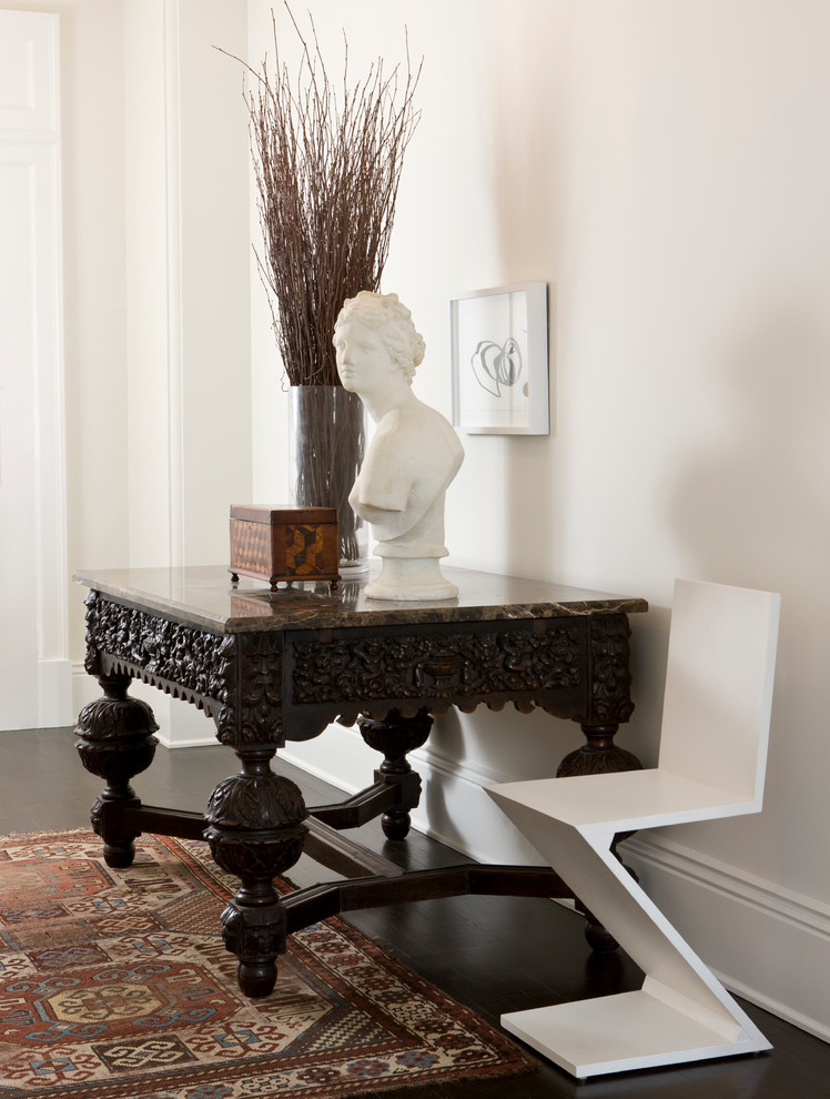 Example of a classic dark wood floor entryway design in Other with white walls