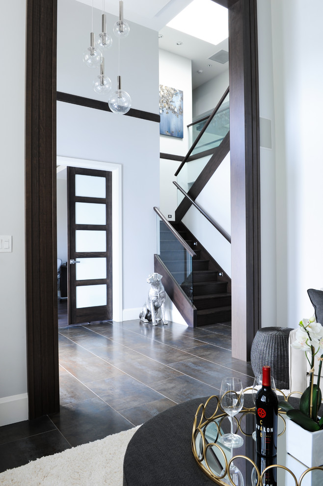 Transitional brown floor foyer photo in Vancouver with white walls