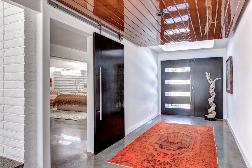 Large trendy concrete floor and gray floor entryway photo in Orange County with white walls and a glass front door