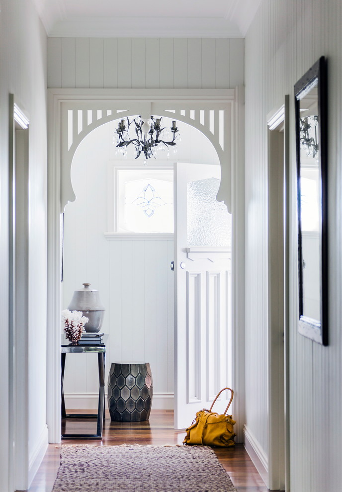 Example of a beach style dark wood floor entryway design in Melbourne with gray walls