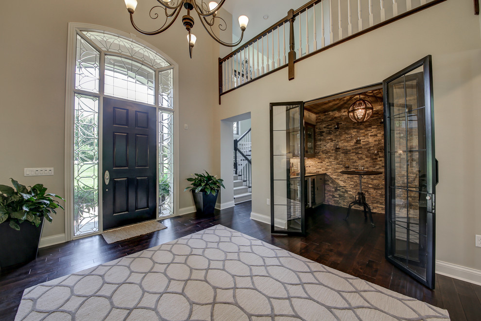 Example of a huge transitional dark wood floor and brown floor entryway design in Dallas with gray walls and a black front door
