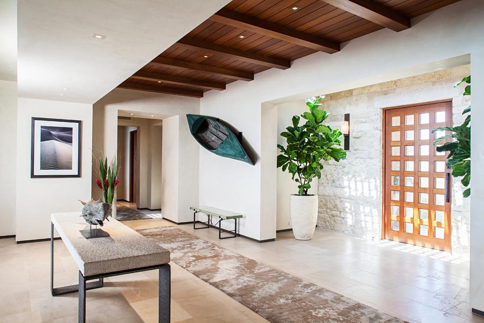 Entryway - contemporary travertine floor entryway idea in Orange County with white walls and a medium wood front door