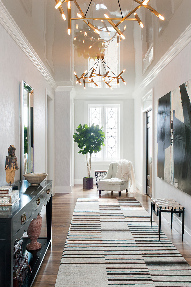 Transitional medium tone wood floor and brown floor entry hall photo in New York with white walls