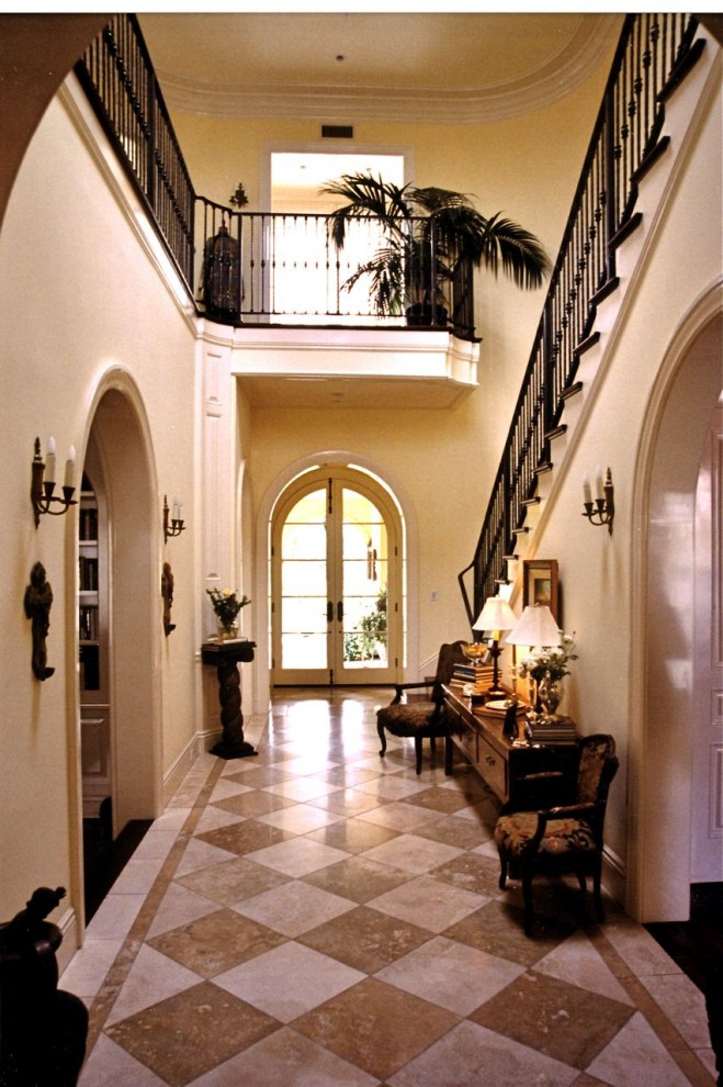 Huge elegant marble floor and beige floor entryway photo in Los Angeles with beige walls and a glass front door