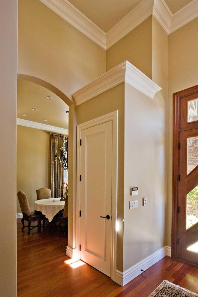 Large eclectic medium tone wood floor and brown floor entryway photo in San Francisco with beige walls and a medium wood front door