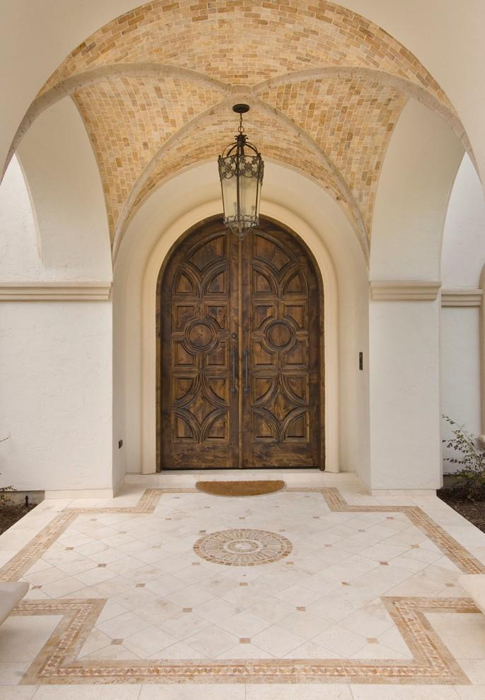 Double front door - mediterranean double front door idea in Houston with a dark wood front door