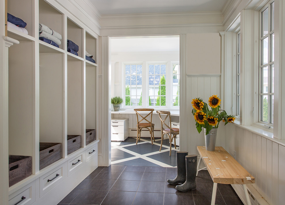 Inspiration for a farmhouse mudroom remodel in Boston with white walls