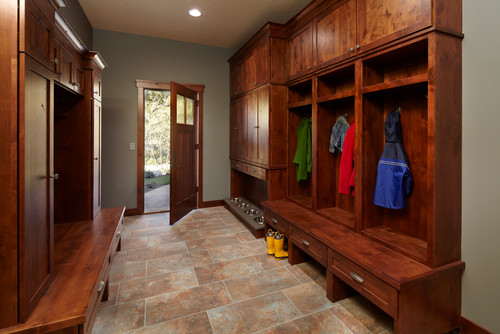 A large rustic mudroom with plenty of locker storage, multiple boot benches and a dog food feeding station.