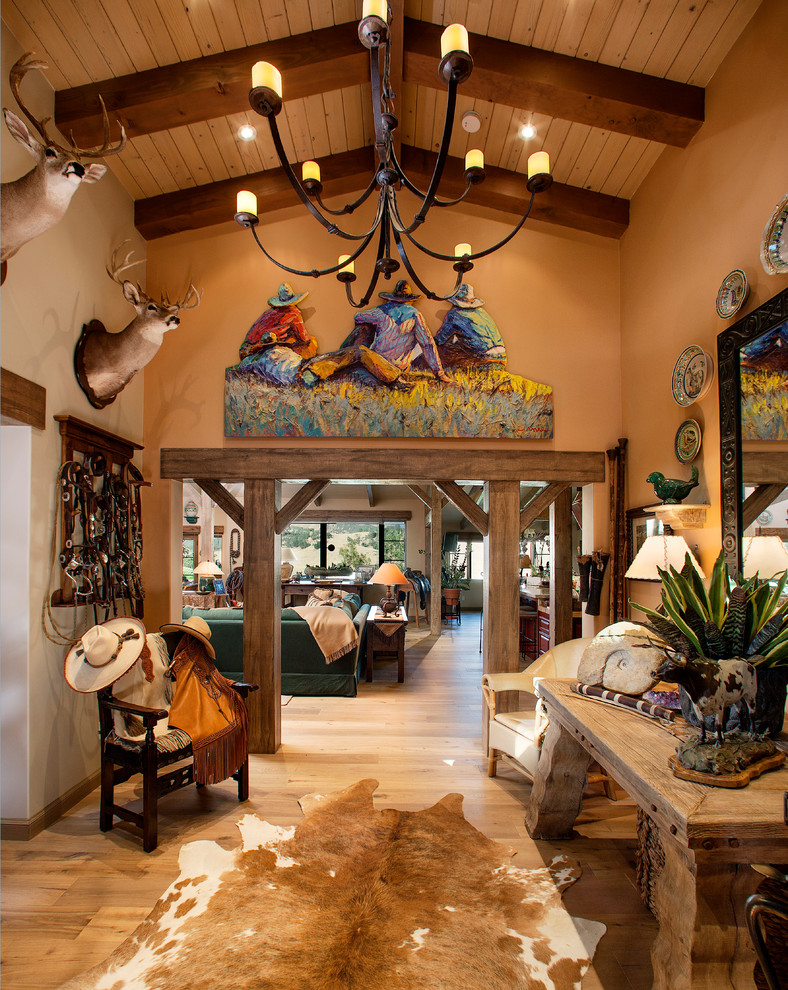 Inspiration for a mid-sized southwestern light wood floor foyer remodel in Santa Barbara with orange walls