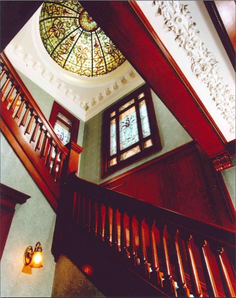 Formal entry with bold stairs and stained glass for light
