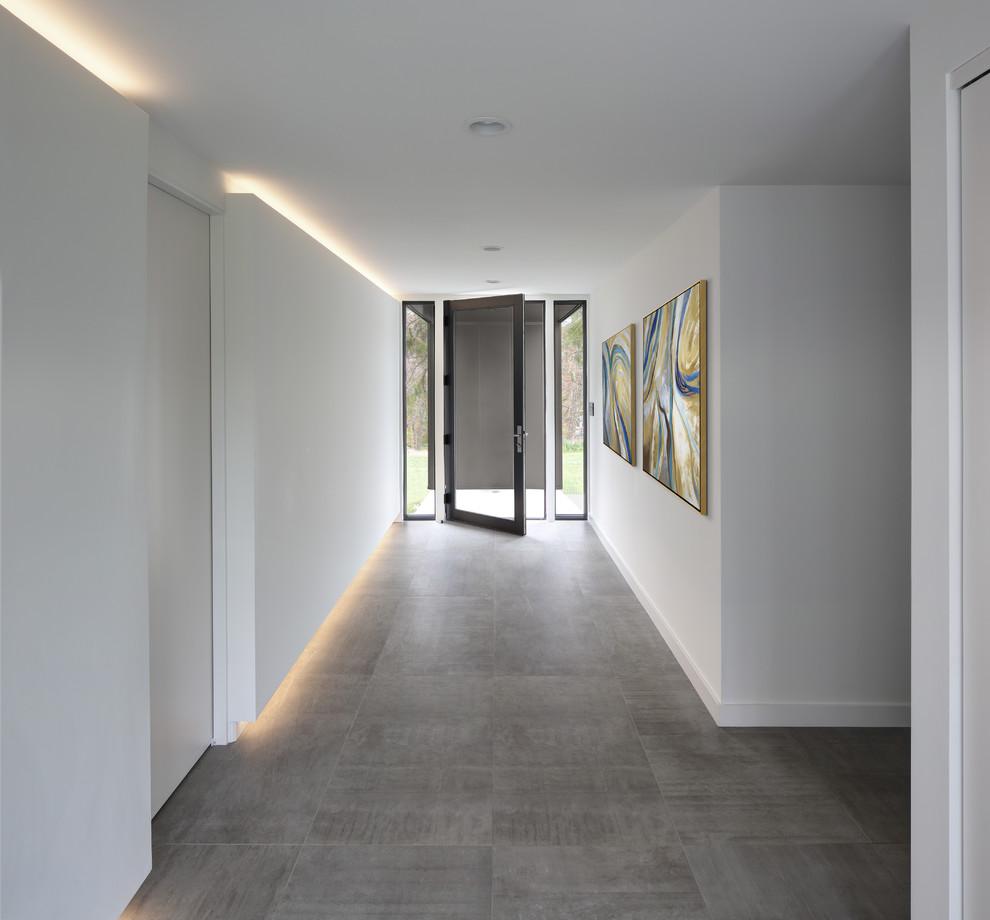 Foto di un corridoio moderno con pareti bianche, una porta singola, una porta in vetro e pavimento grigio