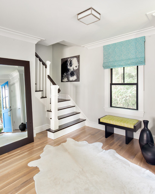 Example of a transitional medium tone wood floor foyer design in New York with gray walls