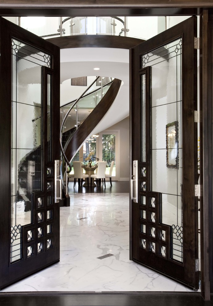 Example of a trendy marble floor entryway design in San Francisco with white walls and a glass front door