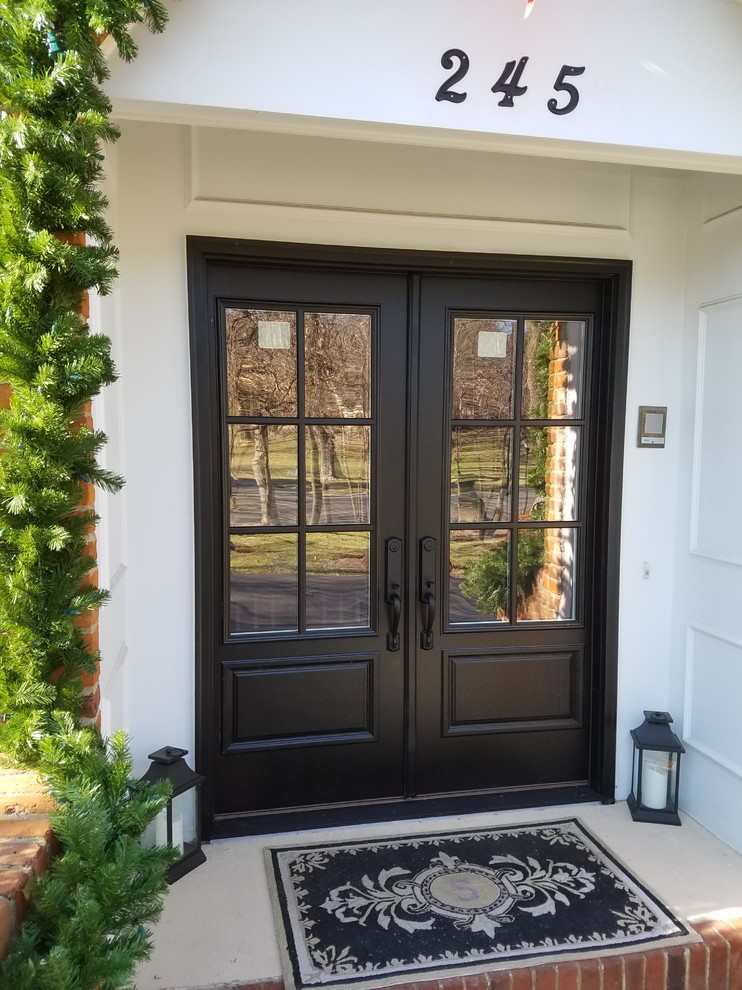 Inspiration for a mediterranean entryway remodel in St Louis with a black front door