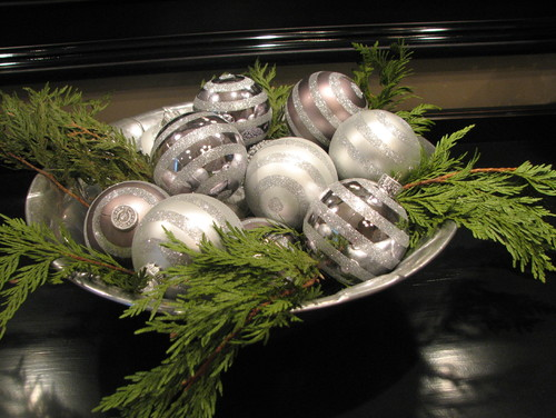 silver Christmas ornaments in silver bowl with pine needles and branches