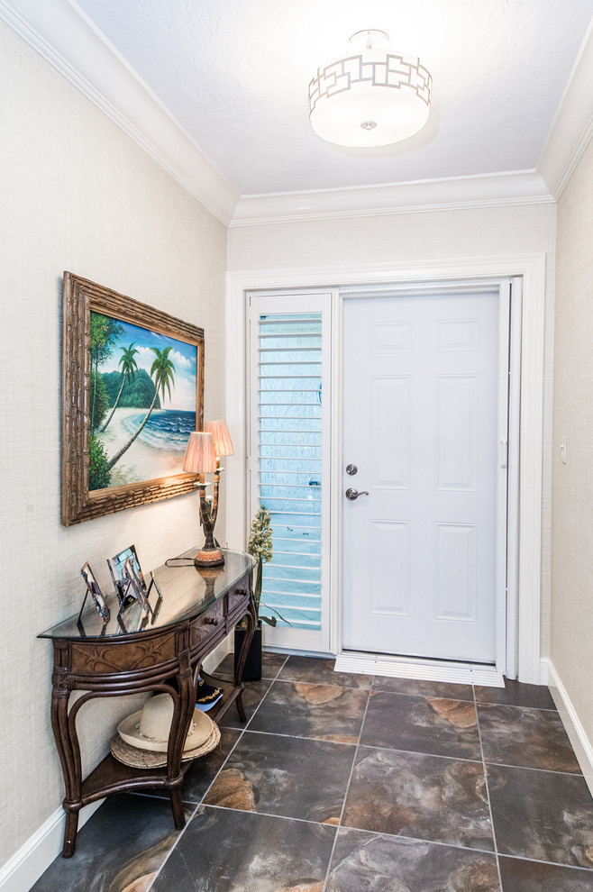 Example of a small beach style entryway design in Miami with white walls and a white front door